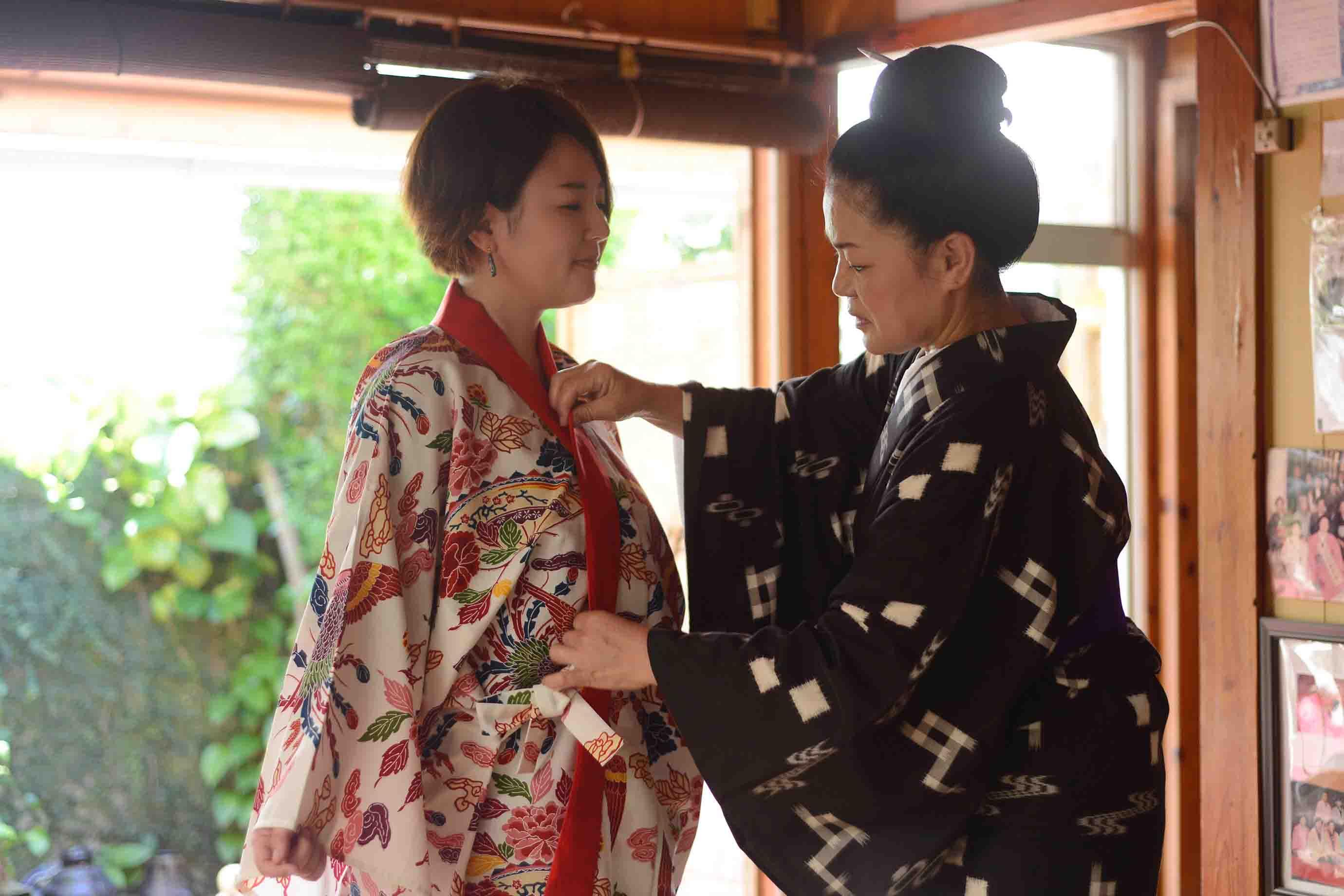 安岡さん (右) に琉球衣装を着付けていただきました。事前の身支度は不要。洋服の上から気軽に羽織るようにまといます