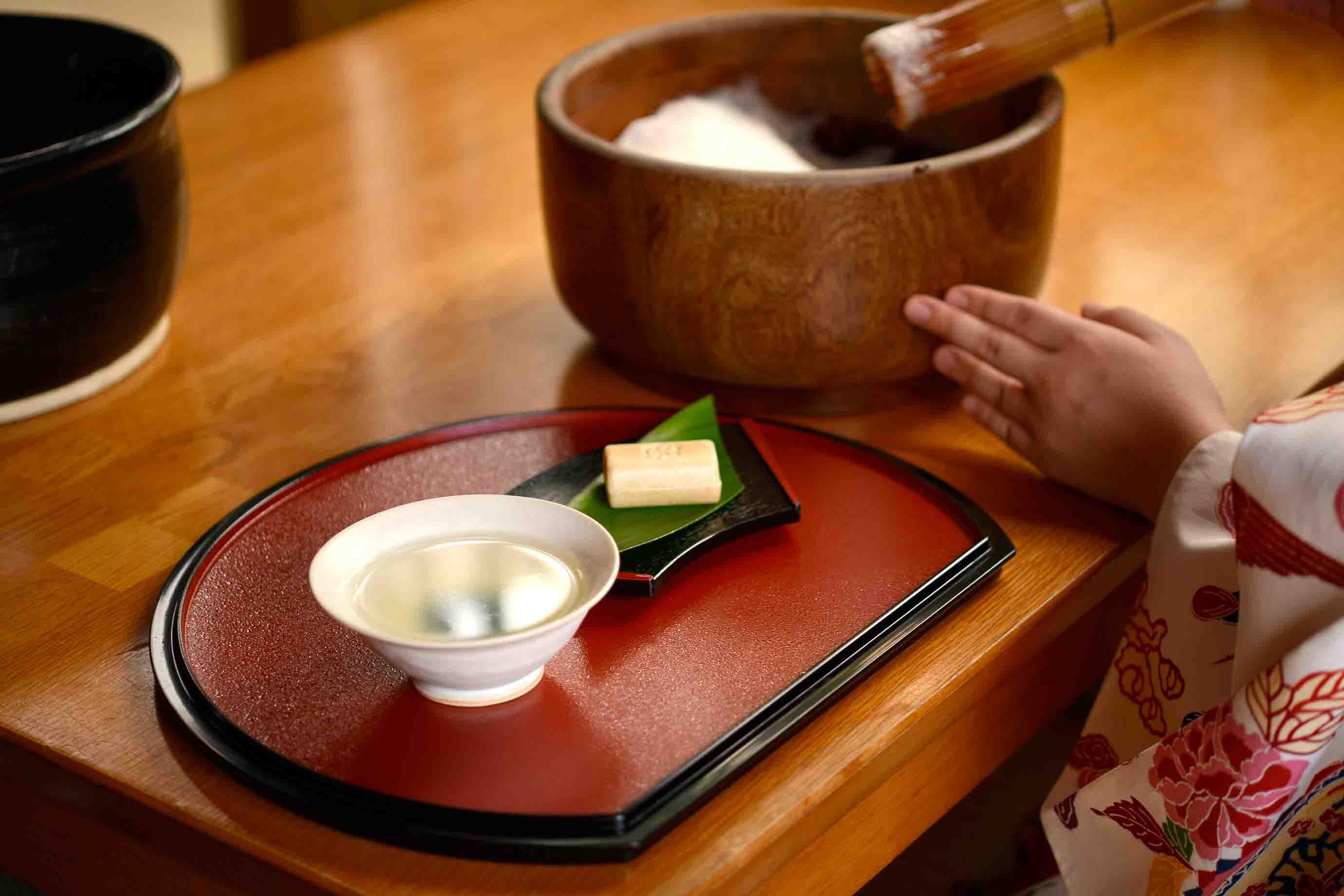 玄米茶を注いだ器と、お菓子を用意して、泡を盛り付けます