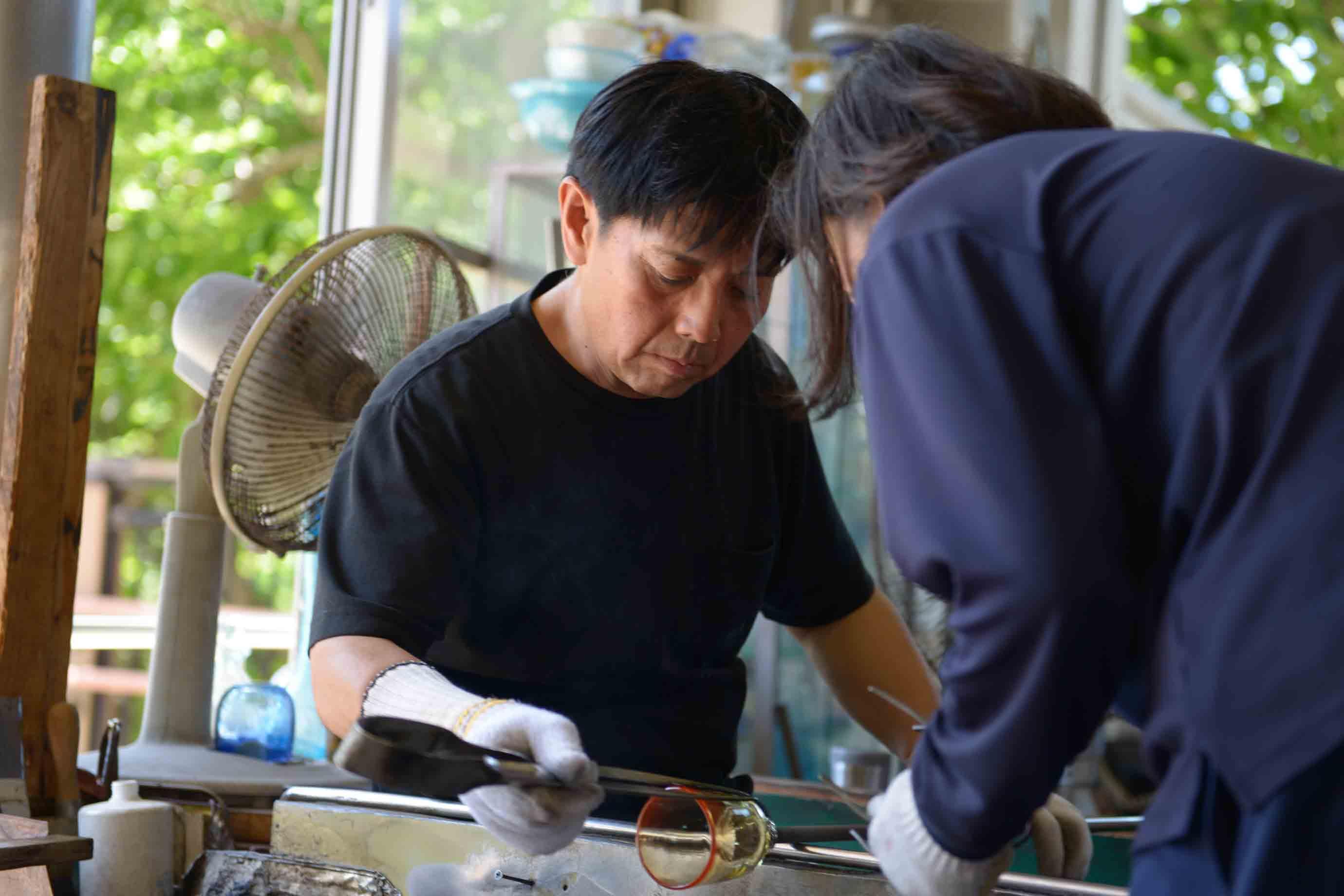 琉球ガラスを職人が2人がかりで製作している