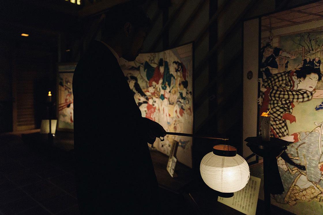 展示室では提灯を手に、祭りの夜さながらに暗闇の中で絵金の屏風絵の複製を見学できる