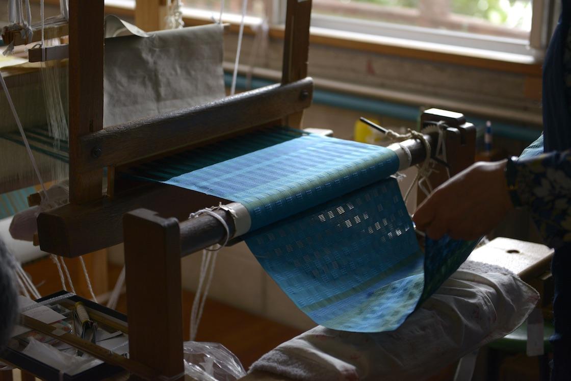 機織り機には織りあがったばかりの布がかかっていました。近づいてみると‥‥