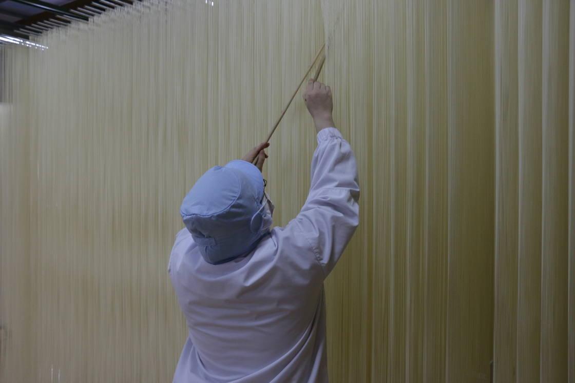 乾燥の工程で麺同士がくっつかず均一な太さになるよう整えているところ
