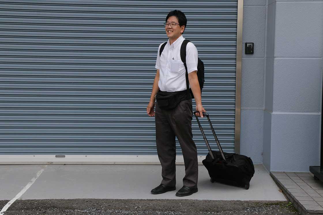 キャスター付きのビジネスバッグとリュックサックで調律に向かう中野さん