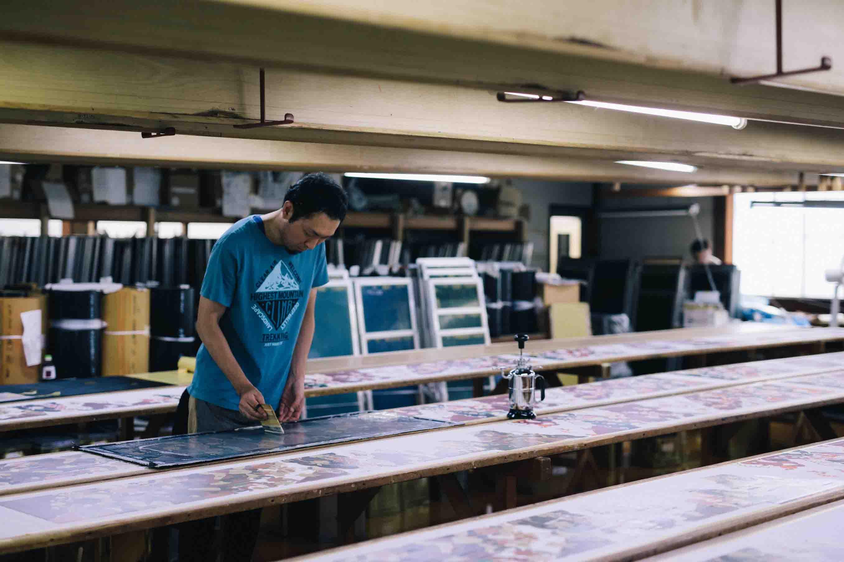 長い板の上に乗せられた白生地に型を当て、1色ずつ染め上げていきます