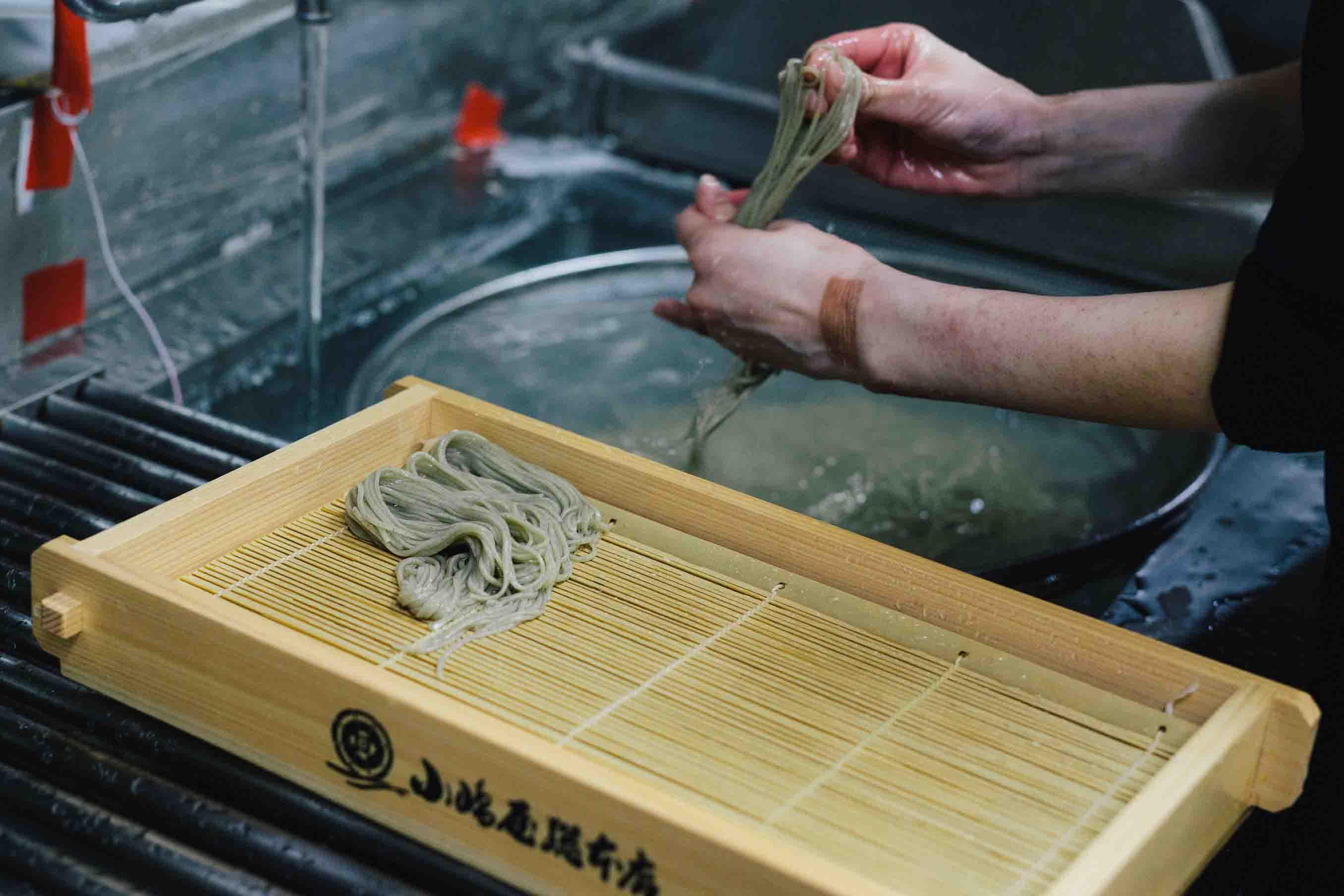 手を振りながら、水から揚げたそばを束ね、八の字に盛り付けます。この様子は、まるで糸を手繰るような動作です
