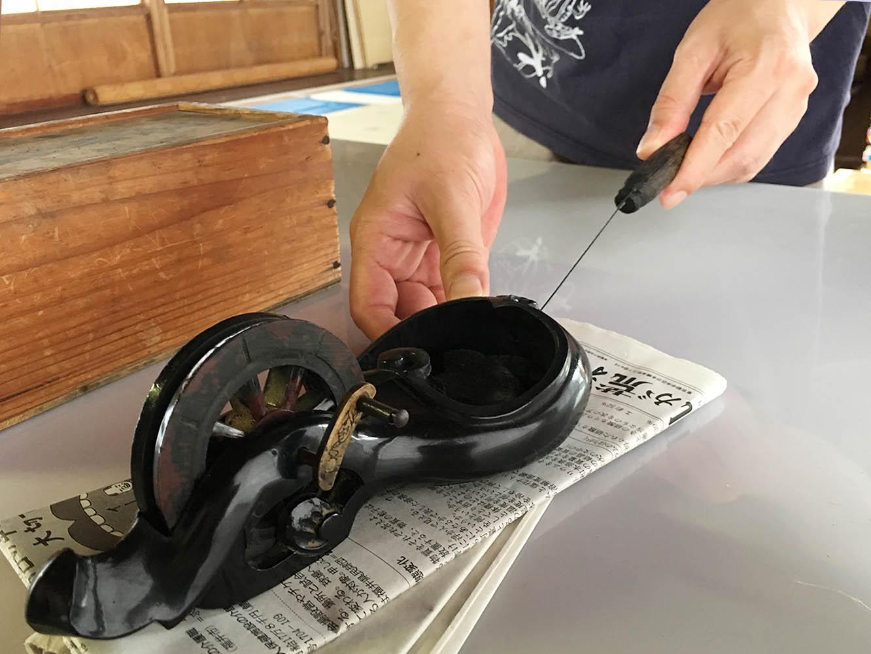 「墨つぼ」。墨のついた糸を引き、糸を弾くことで和紙の上に直線を引きます