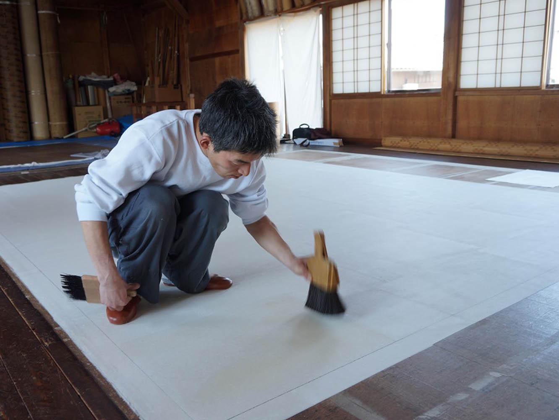1枚貼るごとに重量のある打ち刷毛で「どんどん」と叩き、和紙の繊維を絡み合わせます