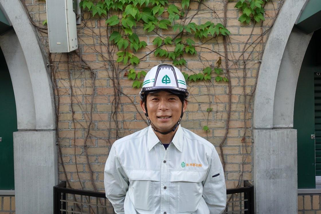 阪神園芸の松本さん。管理している甲子園球場のツタの壁をバックに