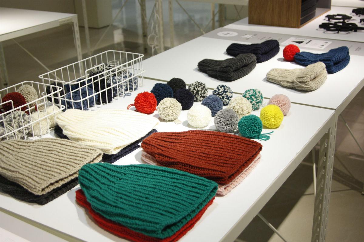 気仙沼ニッティングのニット帽と毛糸の小物。深い緑色やえんじ色などあざやかな色合い。