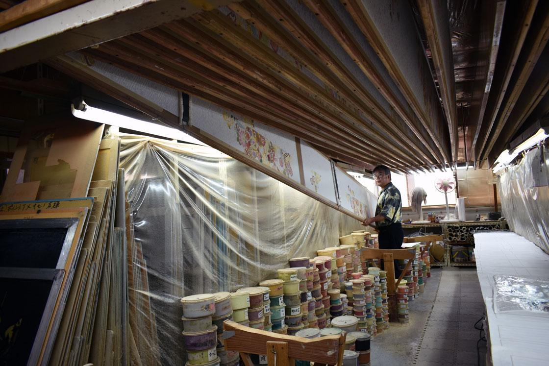 型染めは「友禅板」と呼ばれる全長7mの板に正絹をぴったりと貼り付けておこなわれます。一色染めるごとに友禅板を工房の天井で乾かすのですが、重さ約7kgもの板を上げ下げするのは大変な重労働です