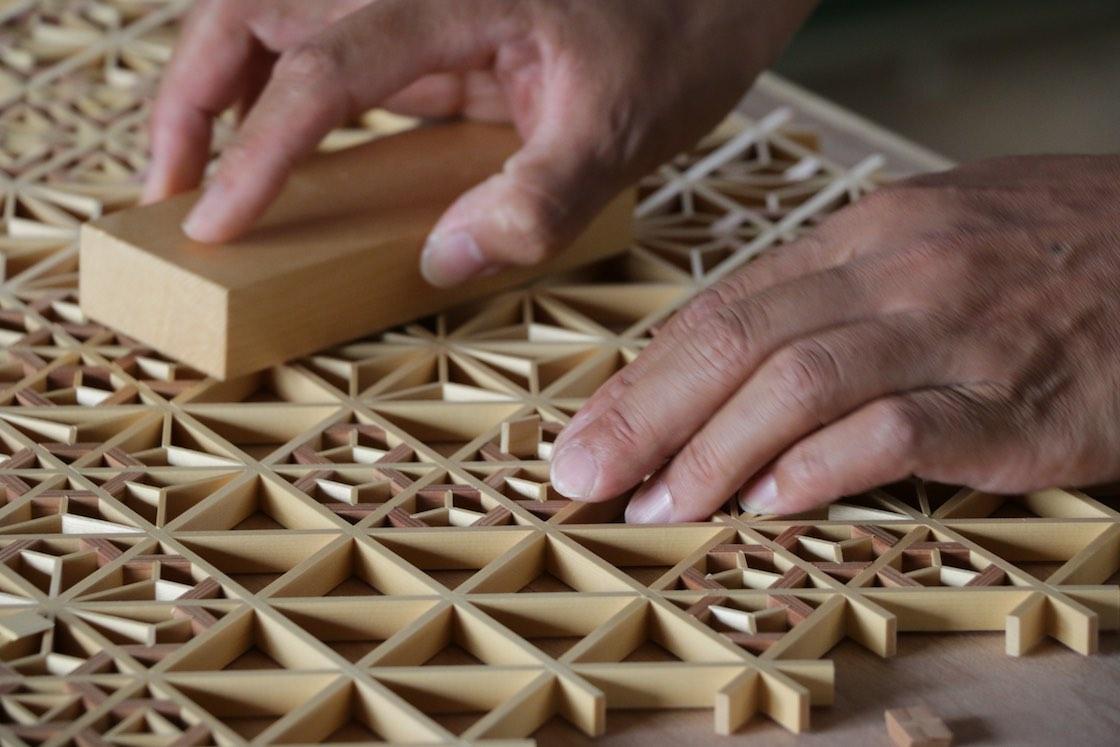 模様を決める最後のパーツは、残りのパーツにしっかり添わせないといけないため、微妙に揺れる人の指はNG。木の板で押し込みます