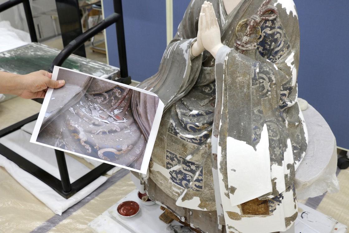 手前の写真は修理前の様子。剥がれ落ちた表面の彩色片が、膝の部分に見受けられる