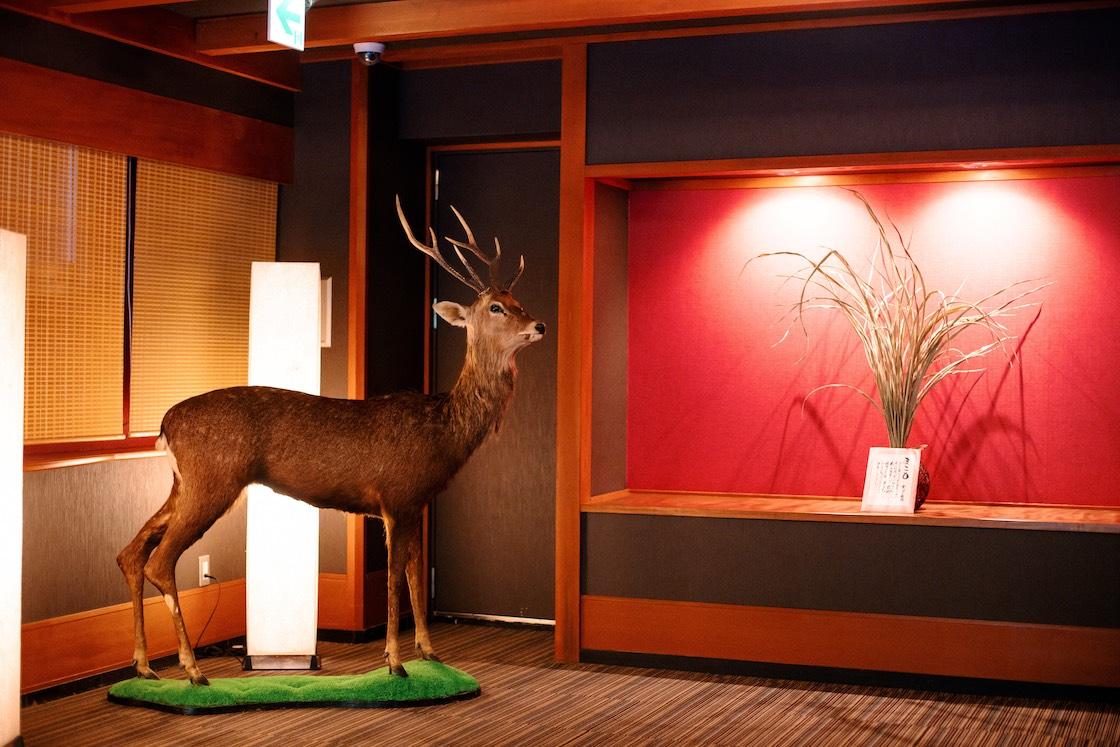 鹿の置物と、右にあるのは菰野町名産の植物・真菰(まこも)