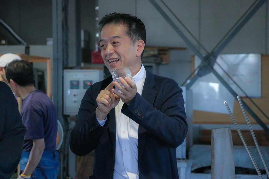 厚さなどが記された製造見本を持つ菅原社長