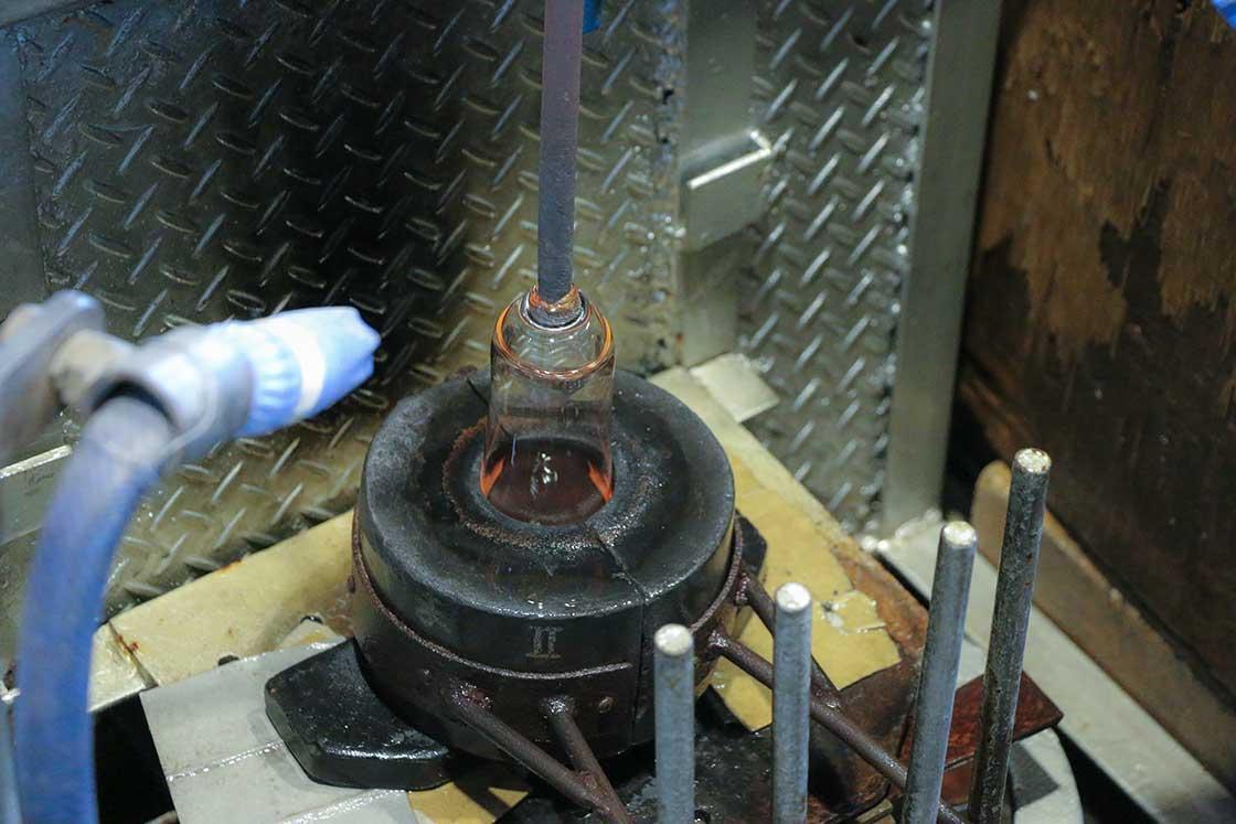 目の前で作られています!炉から竿に巻き取ったガラス玉を型に入れて、空気を吹き入れているところ