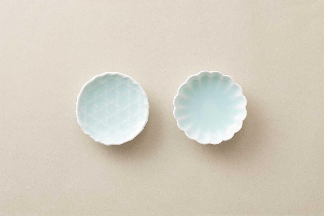 鍋島焼きの窯元「虎仙窯」が手がけた青白磁の豆皿。縁起の良い、食卓が華やぐ「輪花」と、魔除けの効果があるとされる「籠目」模様の2種類
