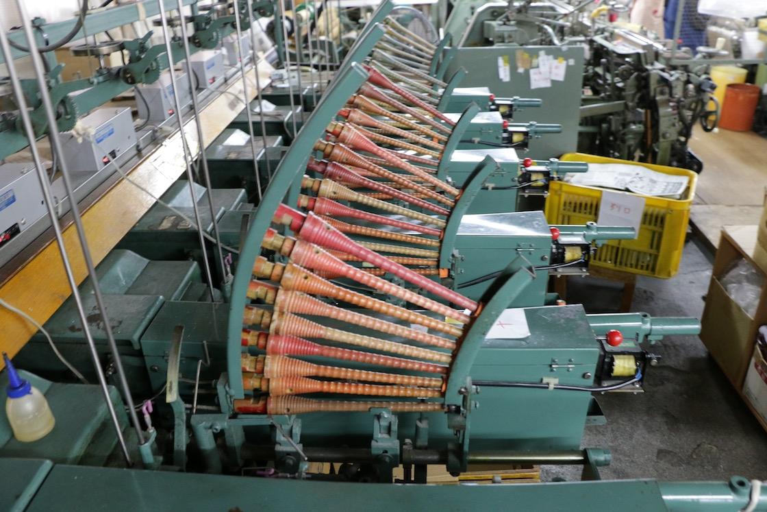 出来上がった糸を巻き取る管の列。全38工程に及ぶものづくりの現場は、普段見慣れない道具やアイディアに溢れています