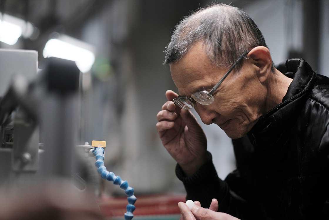 下鶴さんが形を整えた碁石を受け取り、「端引き(はびき)」作業をおこなっていた職人さん