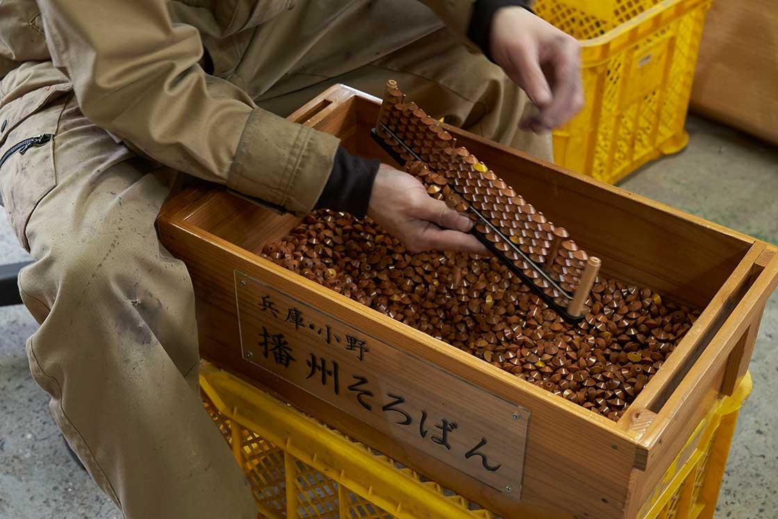 珠を竹ひごに通していく作業