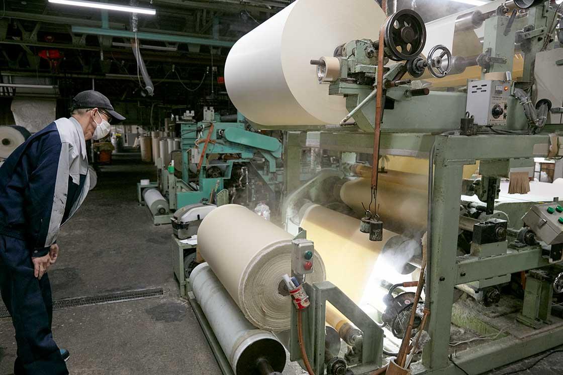 こちらが生地と紙を貼り合わせる機械。わずかなシワや浮きも許されない緊張の一瞬です