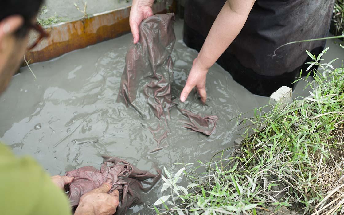 攪拌させた泥にワンピースを深く潜らせ、生地をこするようにして泥をすり込みます