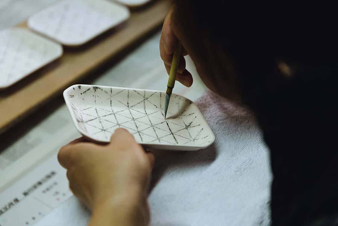 和紙に炭で描いた図柄を器に写してから、呉須で線を描いていく