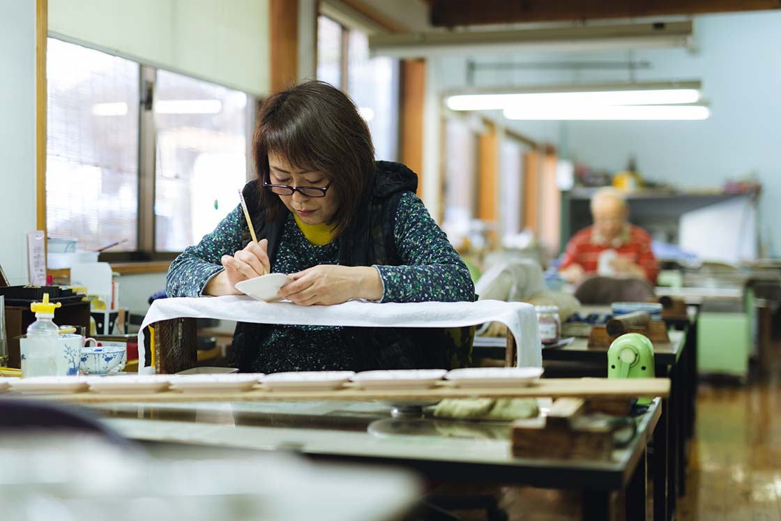 「渓山窯」三代目の篠原祐美子さんが絵付けをしている風景