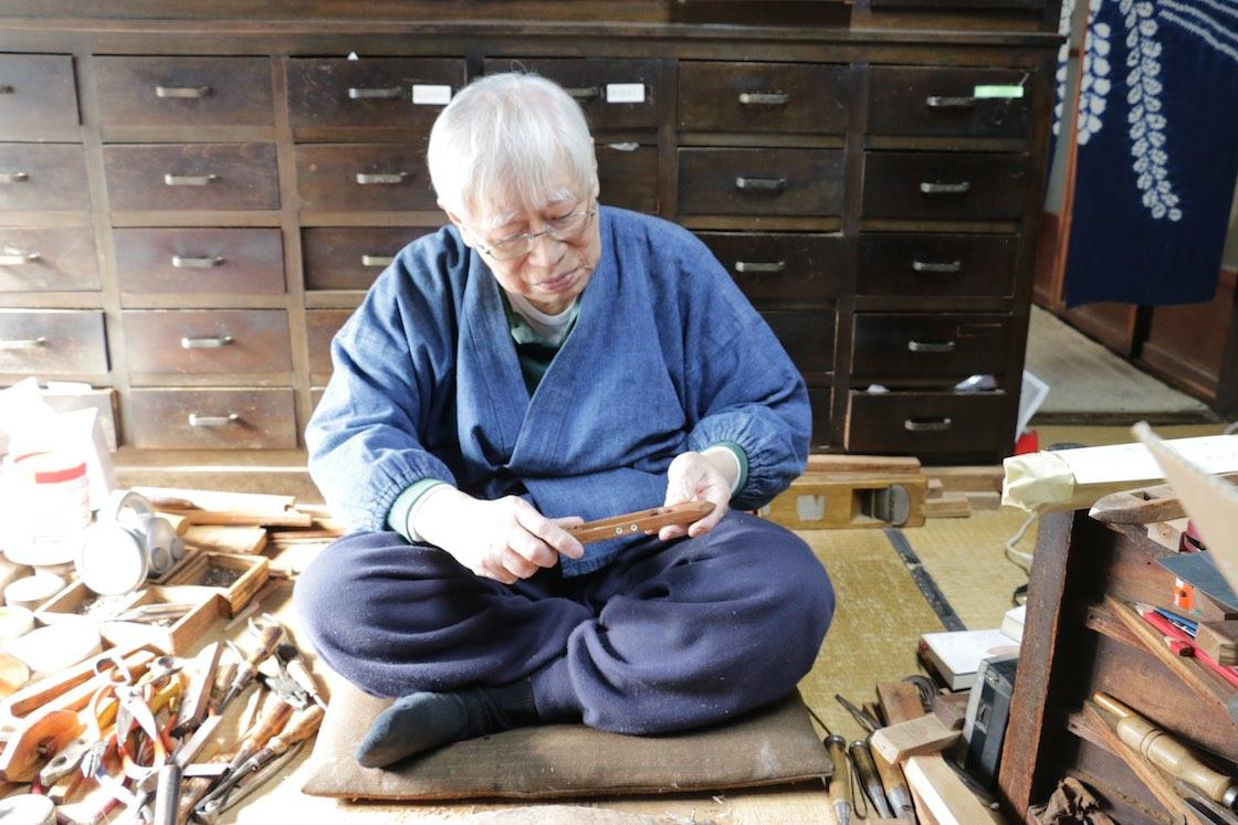 60年以上ものあいだ、杼を作り続けてきた長谷川さん。やはり作務衣が作業しやすいとのこと