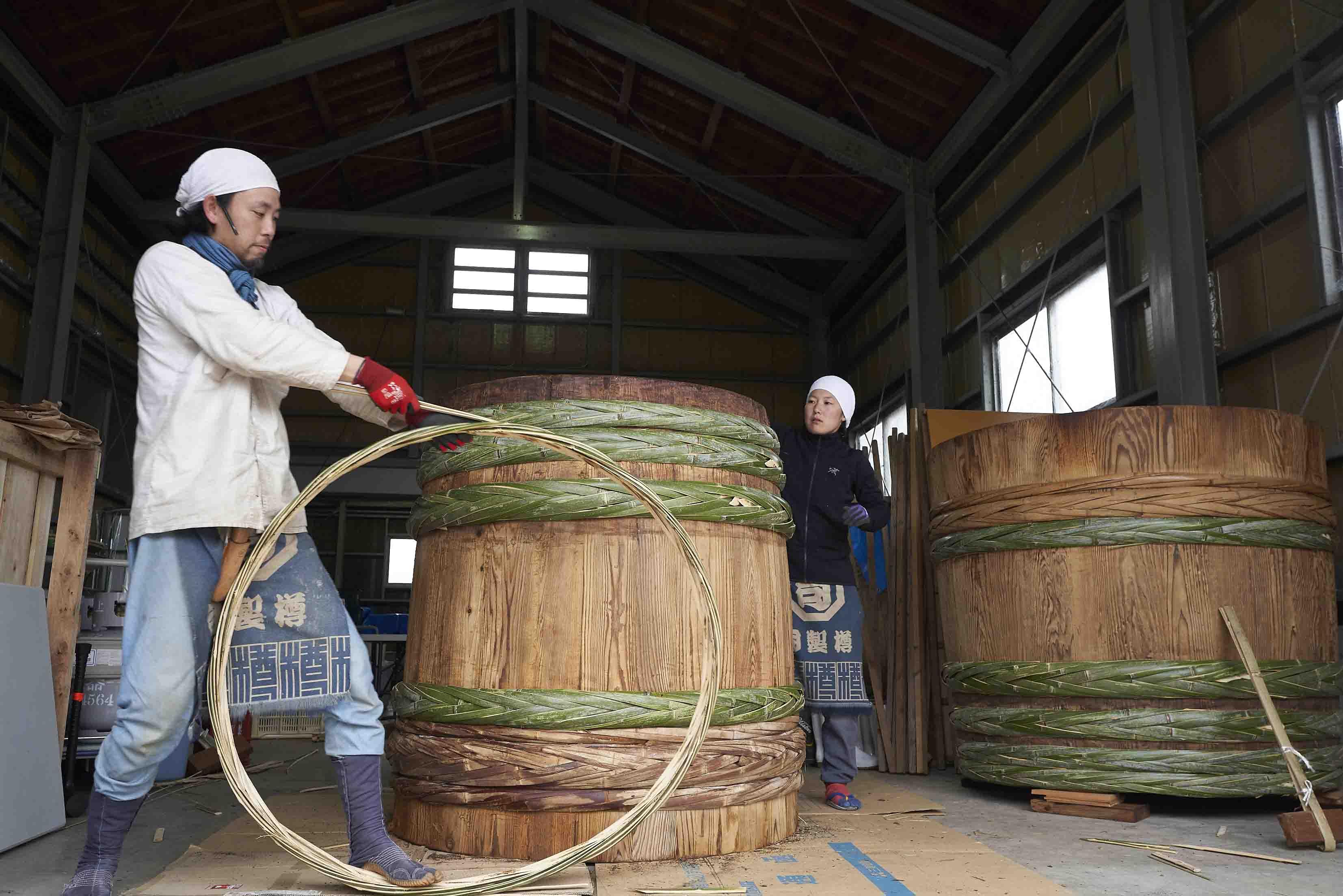 大きな樽を修理する、原田さんと弟子の翠さん