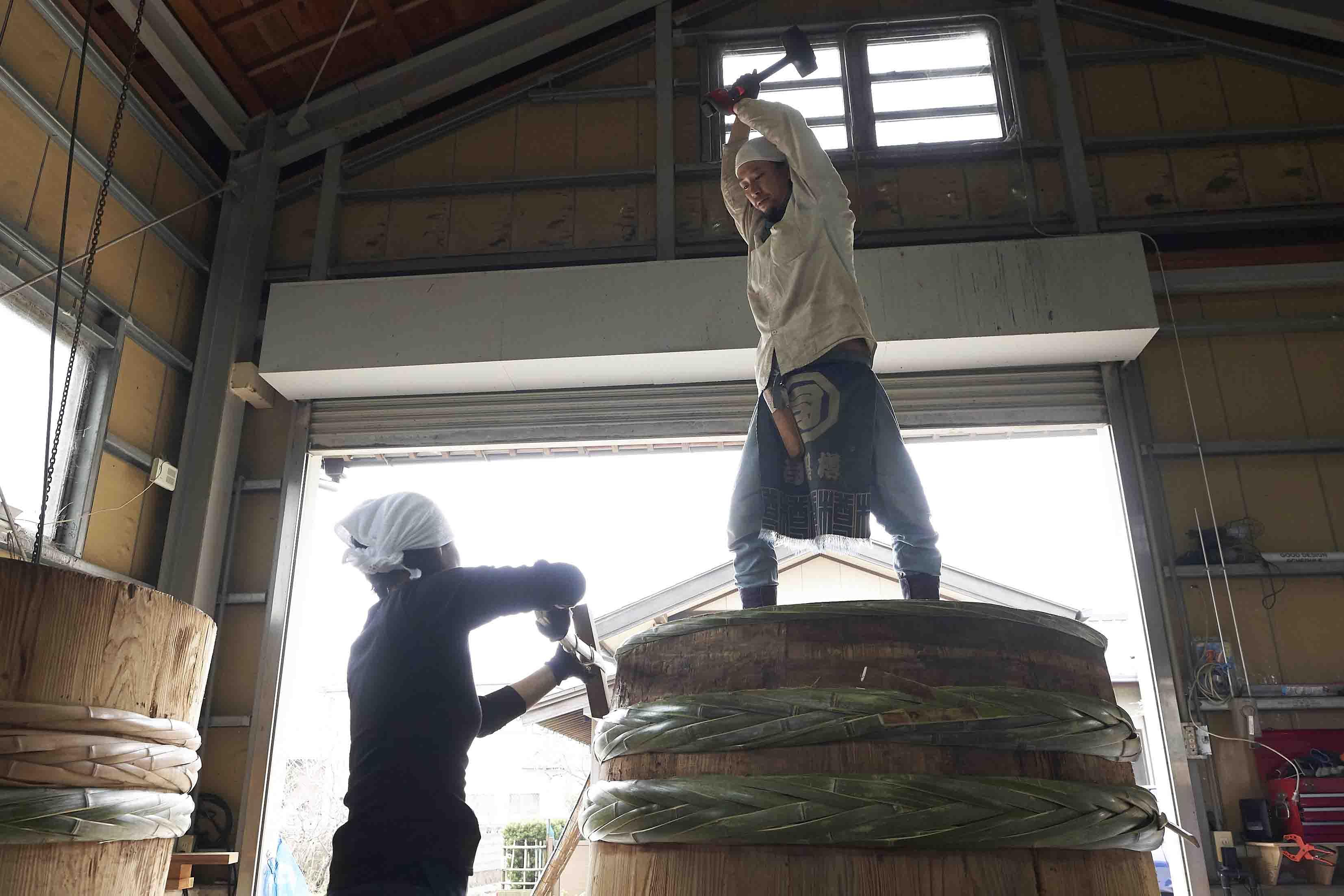 金槌と木槌のようなもので竹の箍を打ち、樽を締め上げていきます