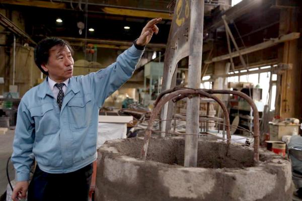 老子製作所の工場内にて。社長の隣にあるのは梵鐘の中子(なかご)と呼ばれるもので、外の型の中に入れ、肉厚を出すためのもの。外の型と中子を組み合わせてできる隙間に金属を流し込んで梵鐘を造る。社長が指差す刃物のようなものは、梵鐘の形にあわせて中子を成型するための引き型
