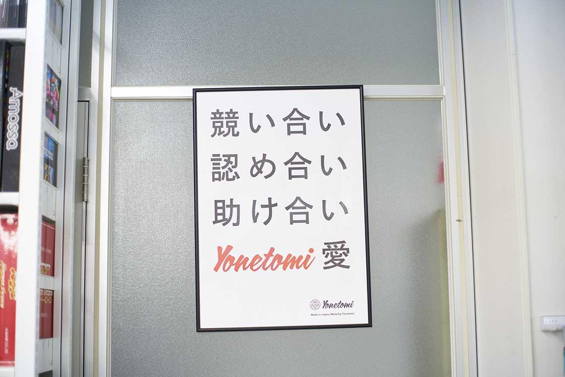 「競い合い認め合い助け合いyonetomi愛」と書かれた米富繊維のポスター