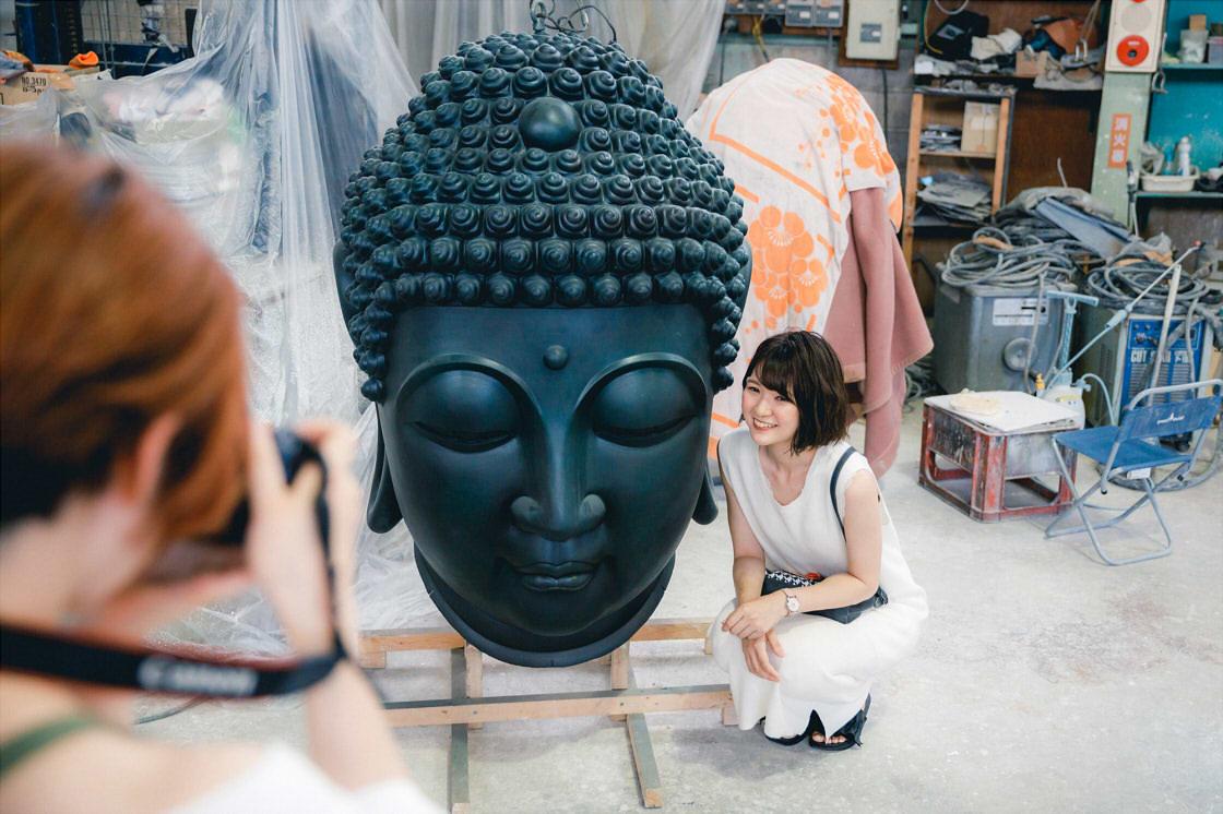 高岡クラフツーリズモ 仏像の頭部と記念撮影する様子