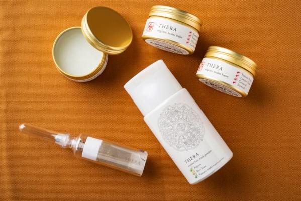 THERAシリーズの商品。上から時計回りに、保湿クリームのマルチバーム、洗顔料の酵素のあらい粉 あお、化粧油のロールオンプレスオイル アロマイン