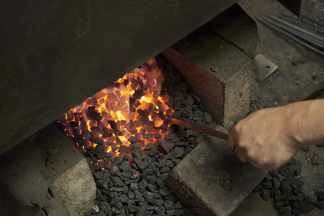 炉に棒を入れる