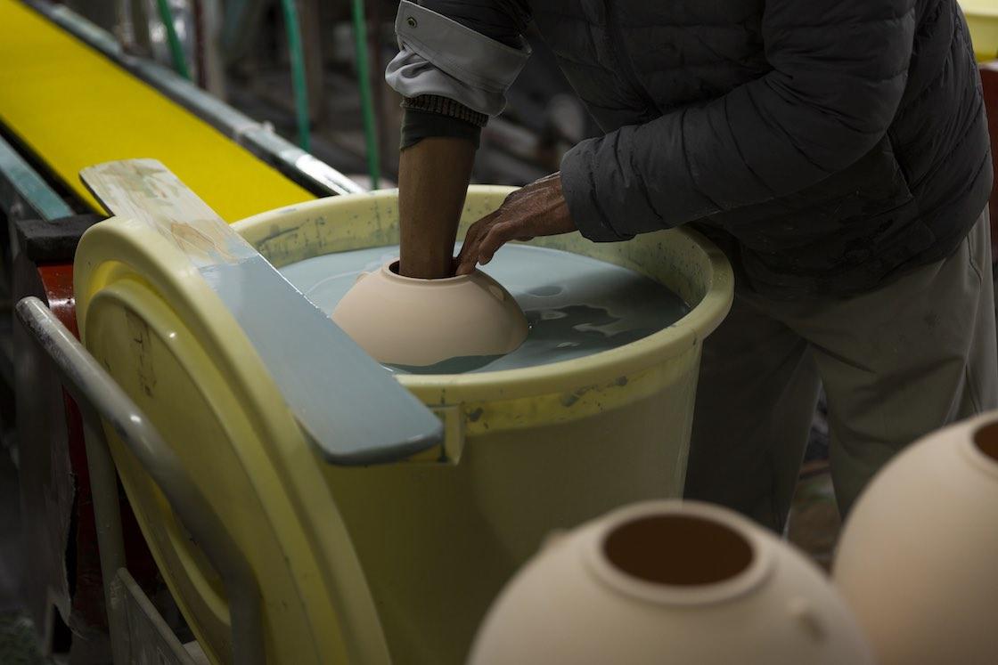 一つひとつ手作業で行う釉薬がけ。こちらは青磁の釉薬をかけているところ