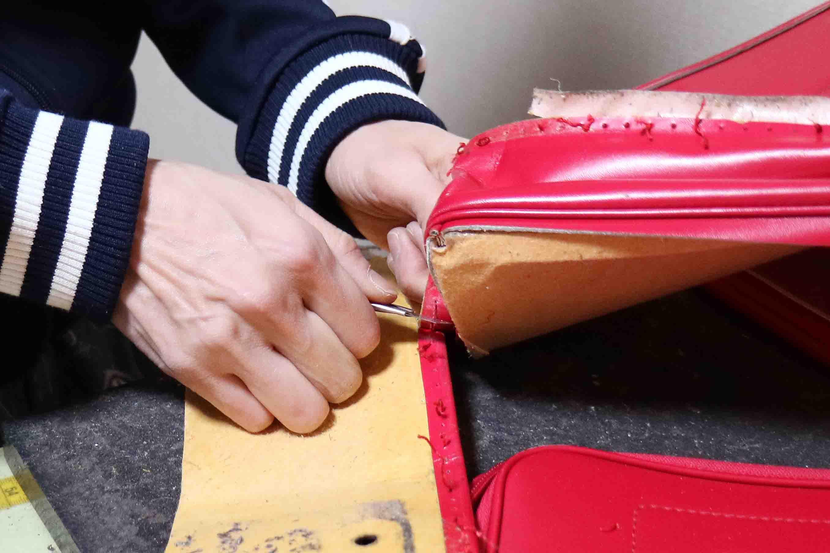 糸を切ることで、革に開けられた糸穴を残しておく。この穴を生かして、最後に手縫いで仕上げると元の雰囲気を残せるのだそう
